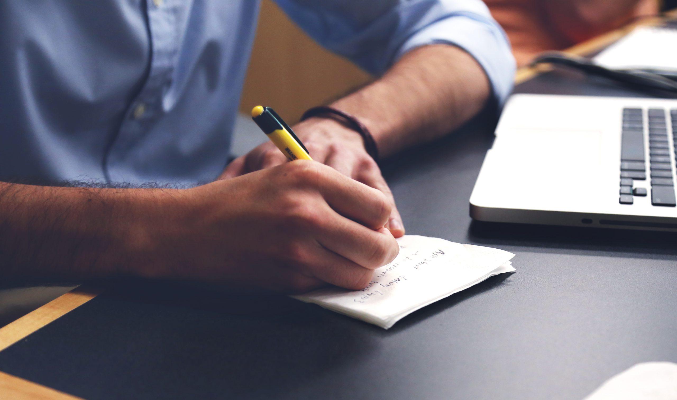 Mann arbeitet mit Laptop und Notizbuch